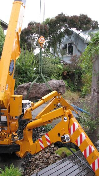 Placing a large rock with a yellow spider crane into a garden
